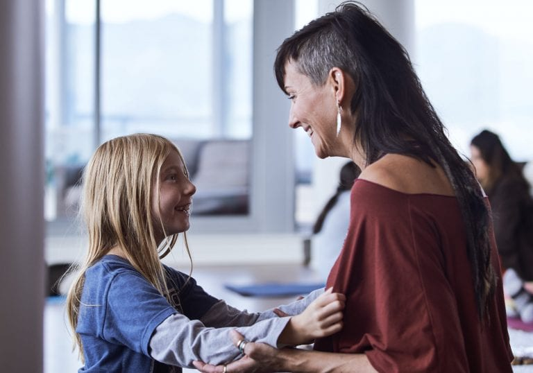 A daughter smiles at her mother as they sit on yoga mats during an exercise at a mother and daughter workshop by Vancouver workshop and retreat photographer Angela McConnell