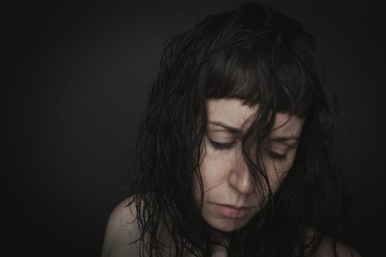 Portrait of a woman with no make up and freckles with hair covering her face
