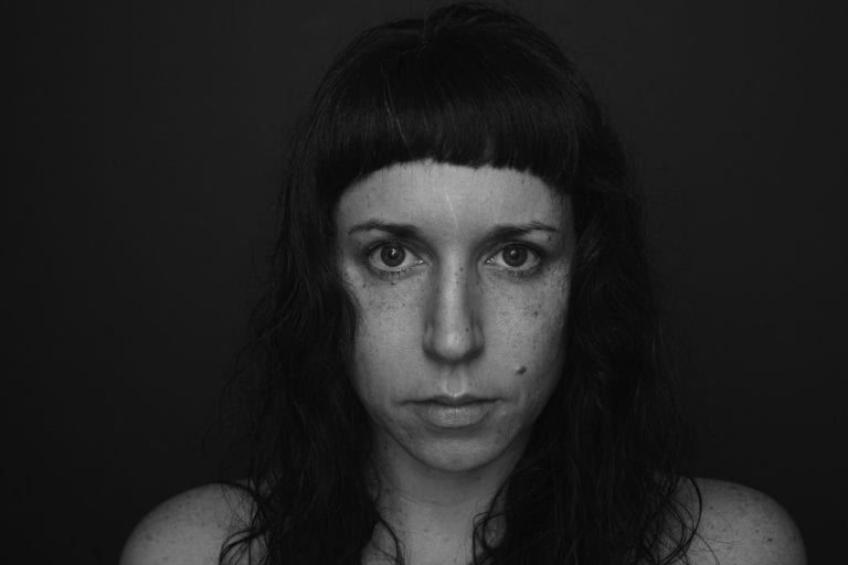 Black and white portrait of a woman with freckles and no make up looking at the camera