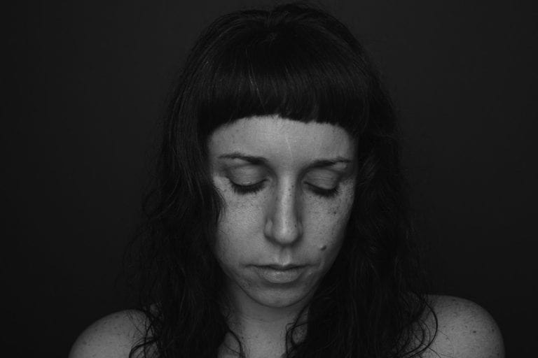 Black and white portrait of a woman with freckles and no make up with closed eyes