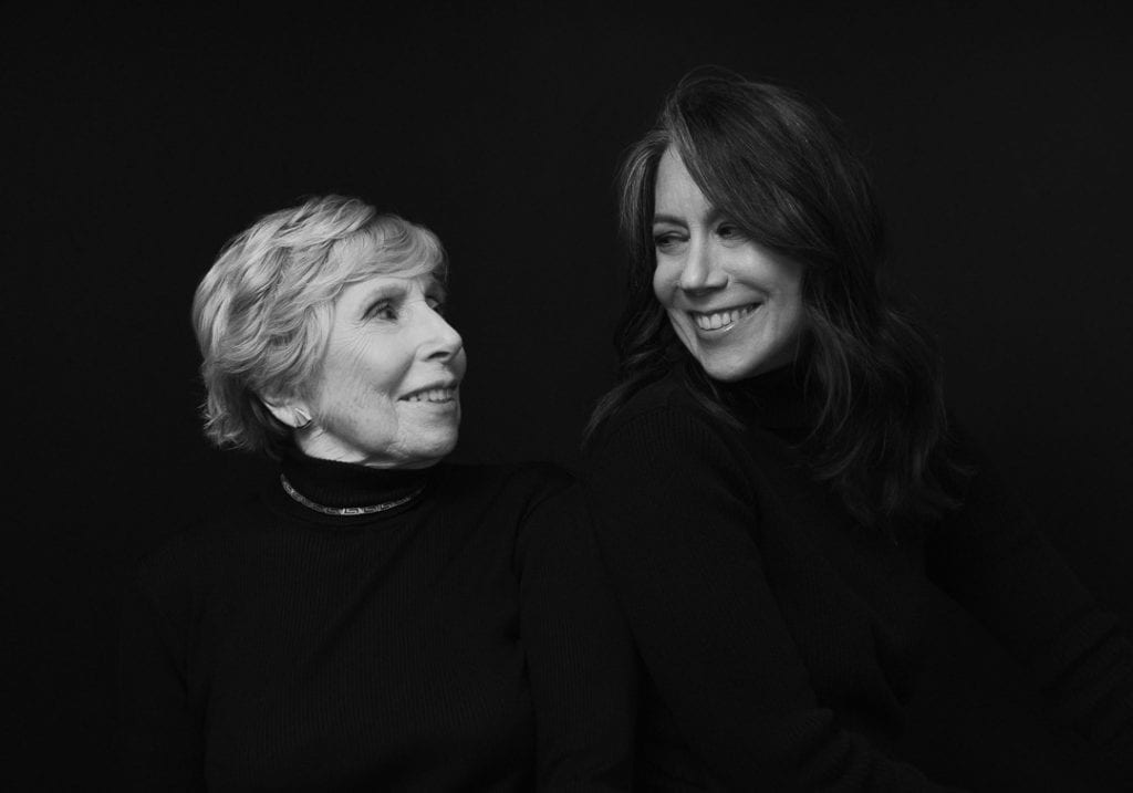 Black and white portrait of an elderly woman with her adult daughter smiling at each other during a mother and daughter session by by Vancouver contemporary portrait photographer Angela McConnell