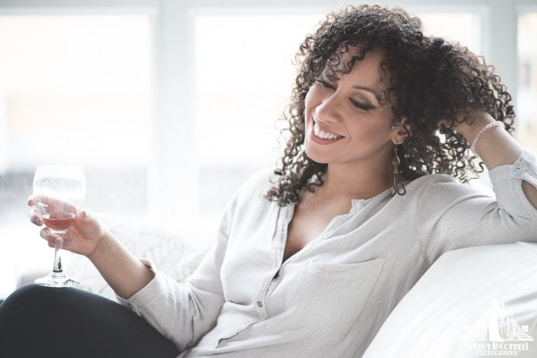 Natural light portrait of a young woman with natural curly hair sitting on a couch with a glass of wine