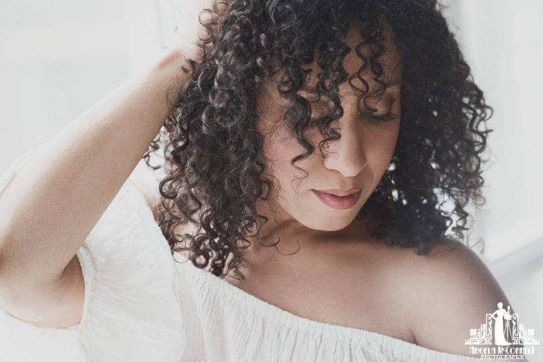 Natural light portrait of a woman with natural curly hair looking down