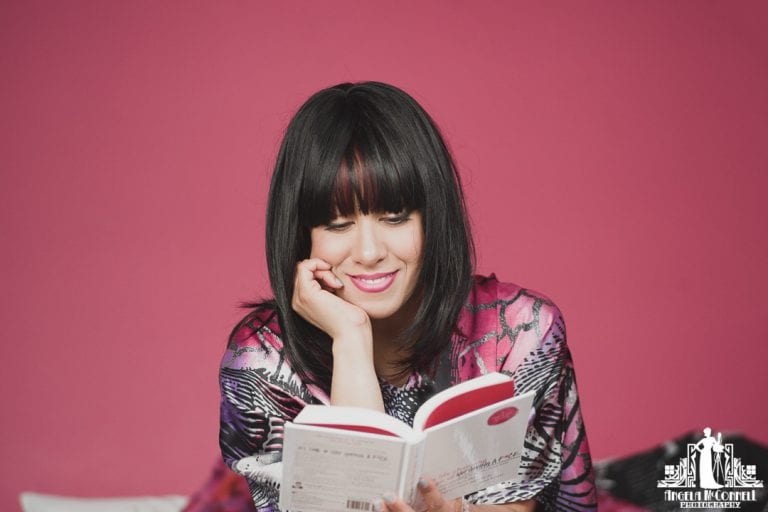 Image of a woman in a colourful caftan reading a book against a bright pink wall