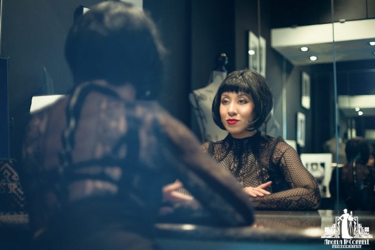 Portrait of a woman in red lipstick looking at her reflection in the mirror