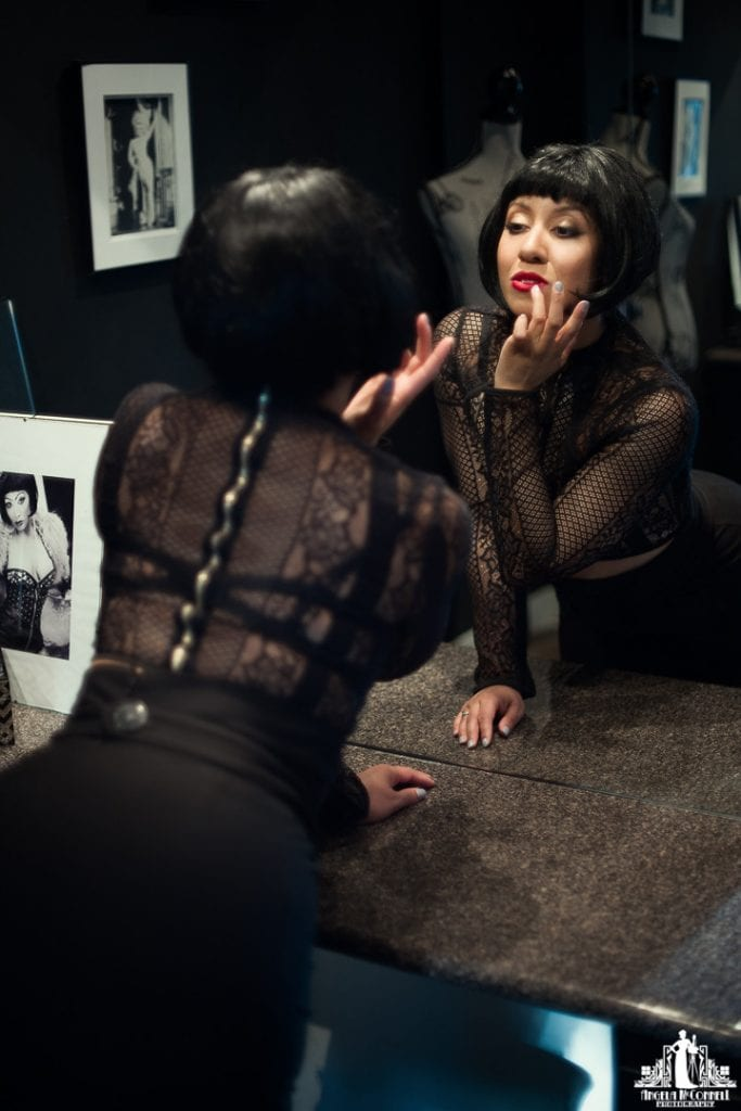 Portrait of a woman checking her red lipstick in the reflection of a mirror