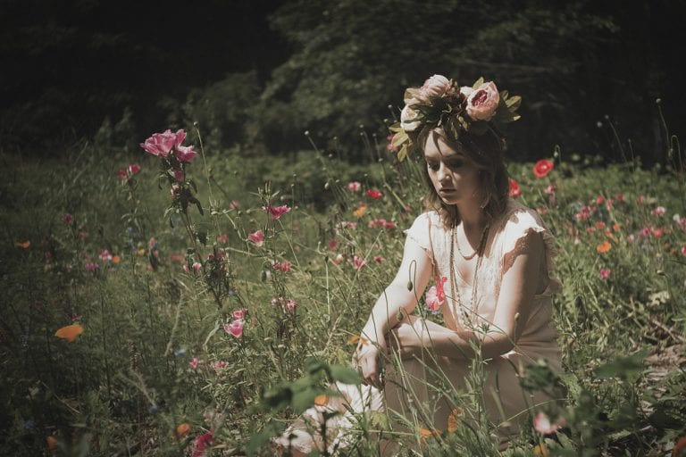 Natural light portrait of a young woman wearing a flower crown seated in a field of wildflowers