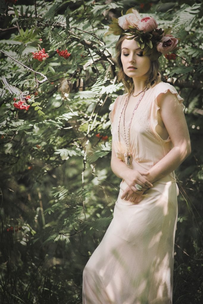 Natural light portrait of a young woman standing in a wooded area wearing a vintage dress and a flower crown