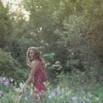 Natural light portrait of a young woman laughing in a field of wildflowers by Vancouver contemporary portrait photographer Angela McConnell