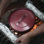 Image of garlic bread wrapped in tinfoil and spaghetti sauce being warmed over a campfire