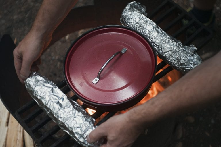Image of garlic bread wrapped in tinfoil and spaghetti sauce being warmed over a campfire at Golden Ears Provincial Park