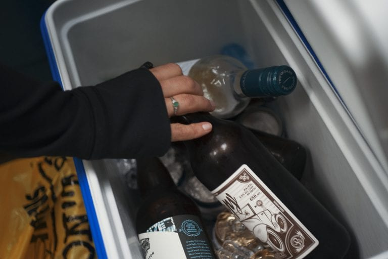 Image of a woman reaching for a beer in a cooler while camping at Golden Ears Provincial Park