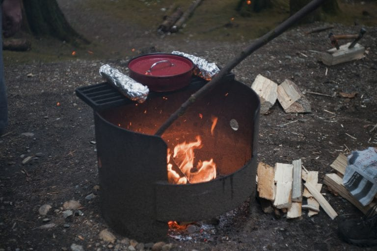 Image of fire being stoked while warming garlic bread and spaghetti sauce while camping at Golden Ears Provincial Park