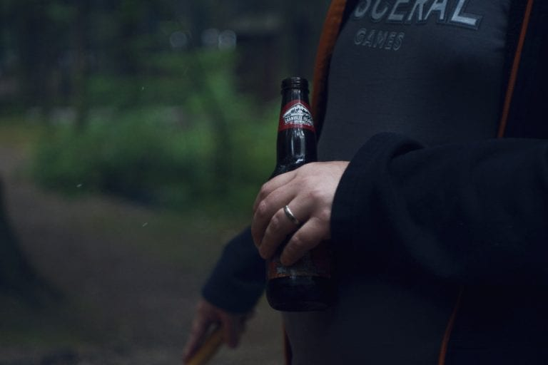 Image of a man drinking beer next to a campfire at Golden Ears Provincial Park