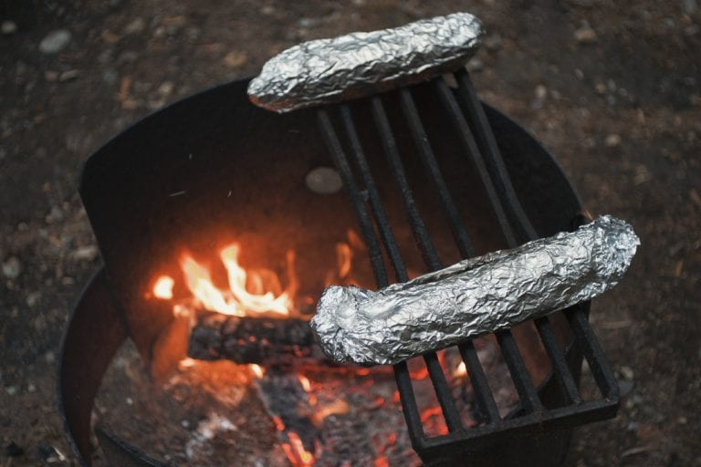 Garlic bread wrapped in tinfoil being warmed over a campfire at Golden Ears Provincial Park