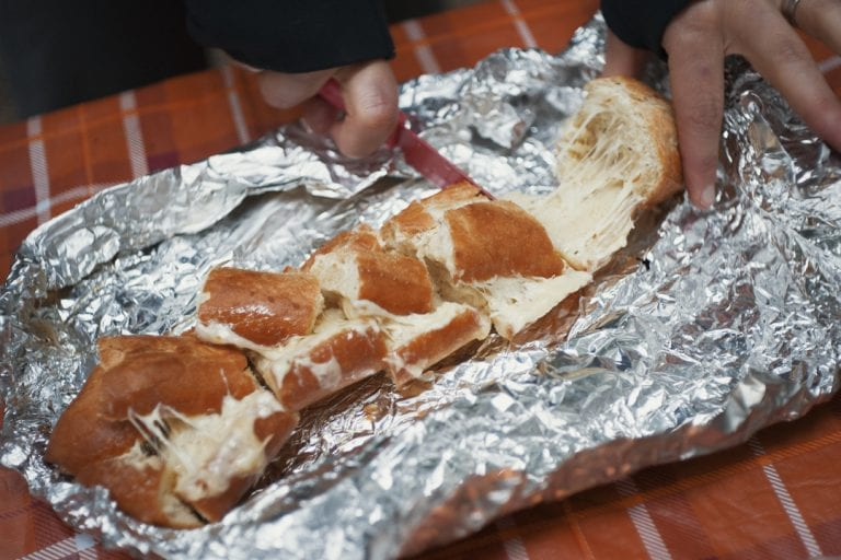 Image of cheesy garlic bread being cut up on tinfoil while camping at Golden Ears Provincial Park