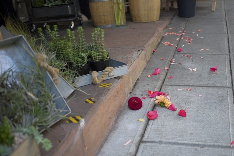 Flowers and petals strewn on the footpath outside a florist in downtown Seattle