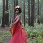 Natural light portrait of a young woman in a red dress and flower crown twirling and smiling at the camera while standing in the forest at Pacific Spirit National Park in Vancouver BC