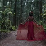 Natural light portrait of a young woman in a red dress and flower crown holding her dress out to the side surrounded by forest in Pacific Spirit National Park in Vancouver BC