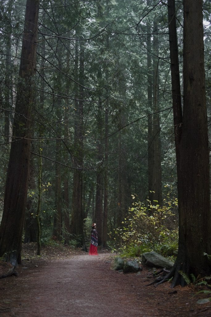 Outdoor portraits at Pacific Spirit National Park in natural light of a young woman in a red dress and flower crown standing in the forest by Vancouver contemporary portrait photographer Angela McConnell