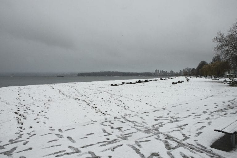 Kitsilano winter wonderland with a view from Kitsilano Beach with footprints crossing the snow across to Stanley Park and West Vancouver on a snowy day in Vancouver BC