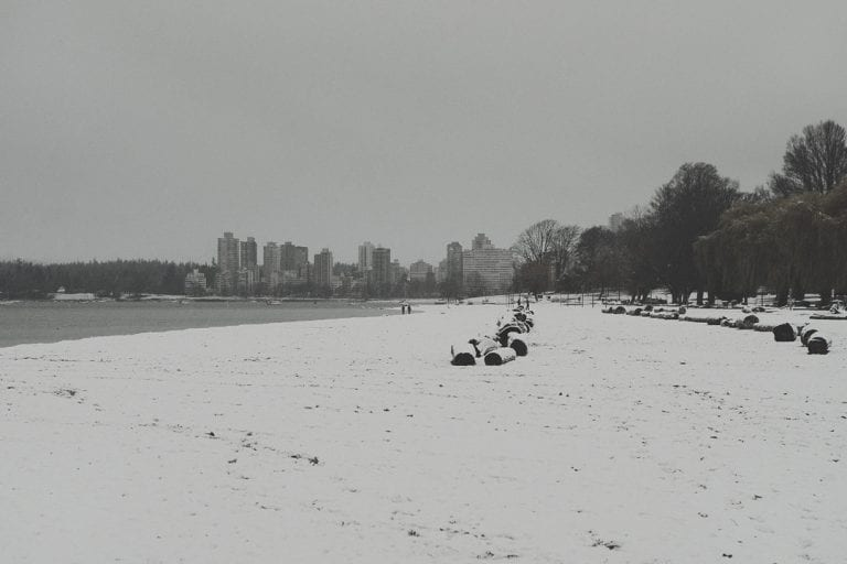 Kitsilano winter wonderland from the beach looking across to English Bay on a snowy day in Vancouver BC