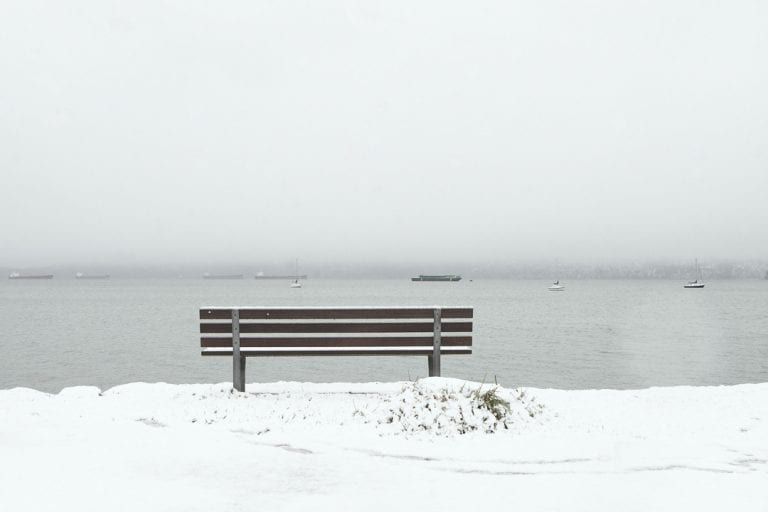 Kitsilano winter wonderland with a park bench overlooking the water at Kitsilano Yacht Club looking towards West Vancouver on a snowy day in Vancouver BC