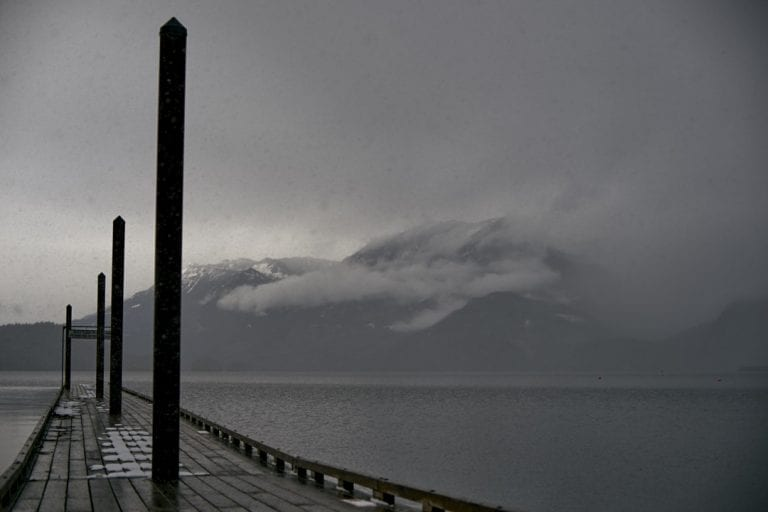 Moody image of snow falling on a pier leading onto a lake with cloud covered mountains in the background