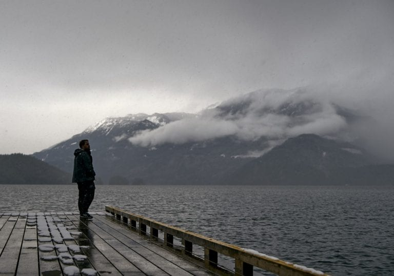 Moody image of a bearded man standing on a pier on Harrison Lake looking across to snow and cloud covered mountain ranges in the distance