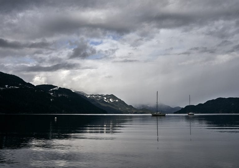 Moody image of sailboats moored at anchor in Harrison Lake with snow and cloud covered mountains in the background