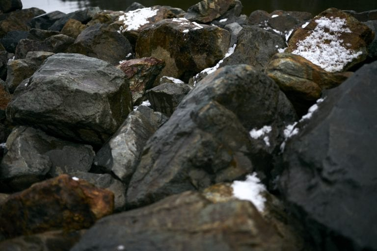 Moody images of rust streaked boulders covered in a dusting of snow on a breakwater at Harrison Lake