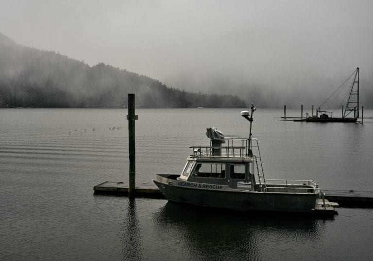 Moody image of the Search and Rescue boat at the marina on Harrison Lake while birds fly across the water with cloud covered mountains in the background