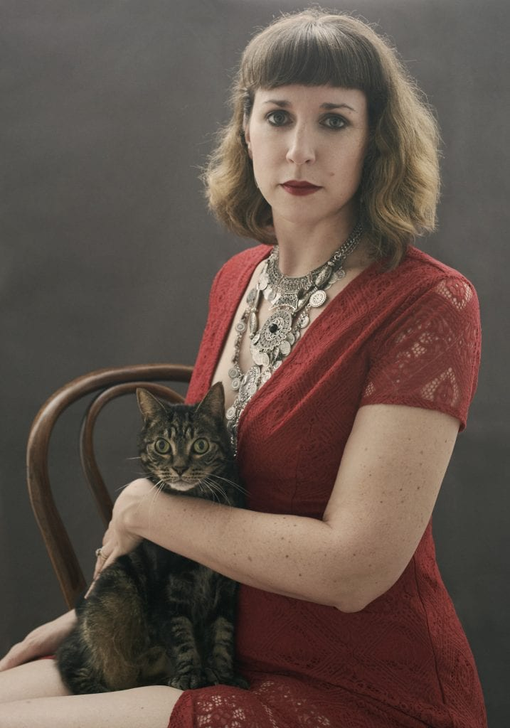 Birthday portraits of a woman in a red dress with stacked silver necklaces and red lipstick holding a wide eyed tabby cat by Vancouver contemporary portrait photographer Angela McConnell