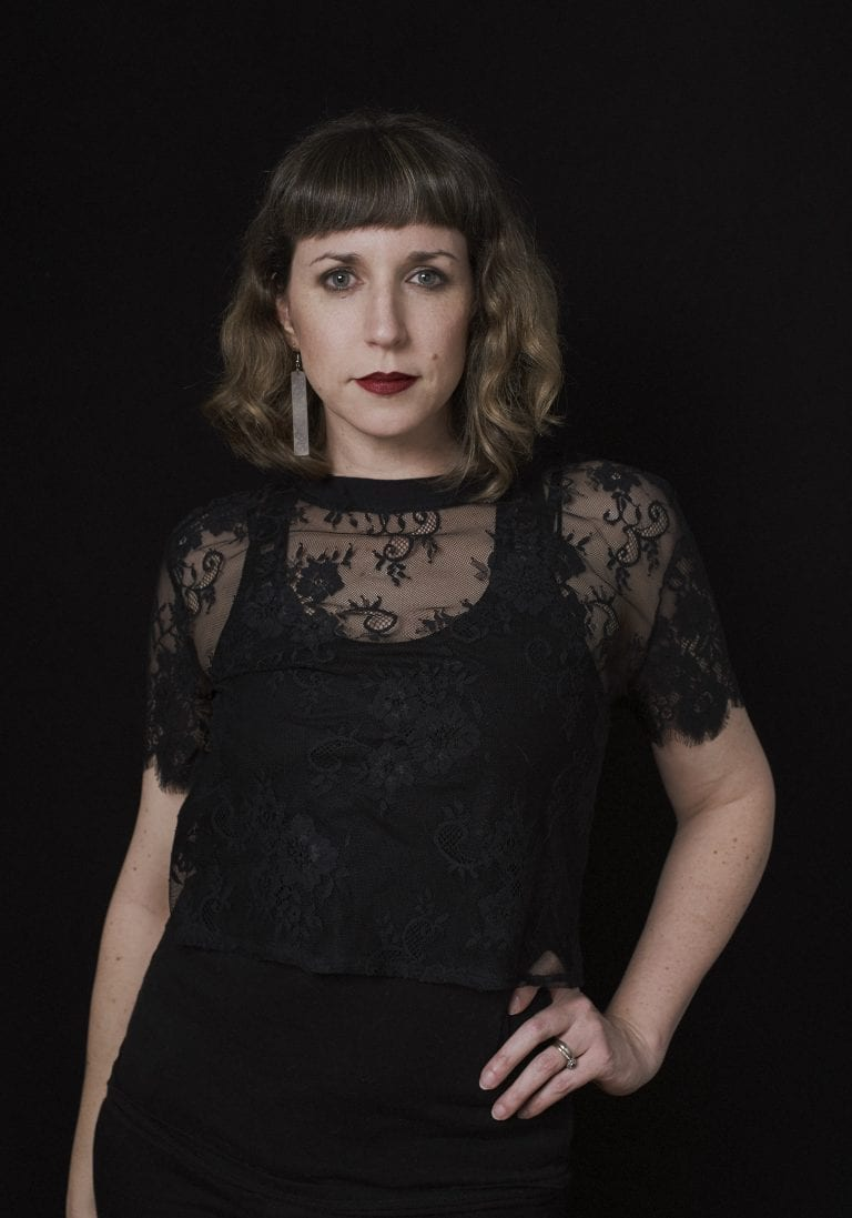 Birthday portraits of a woman in a black lace top with red lipstick looking the camera on a black background by Vancouver contemporary portrait photographer Angela McConnell