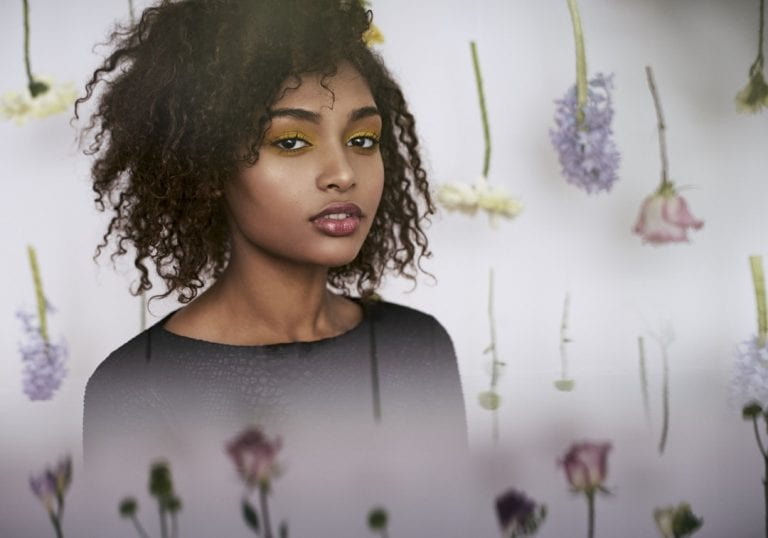Spring creative studio portraits of a young woman with natural hair sitting in front of a wall of hanging spring blooms by Vancouver contemporary portrait photographer Angela McConnell
