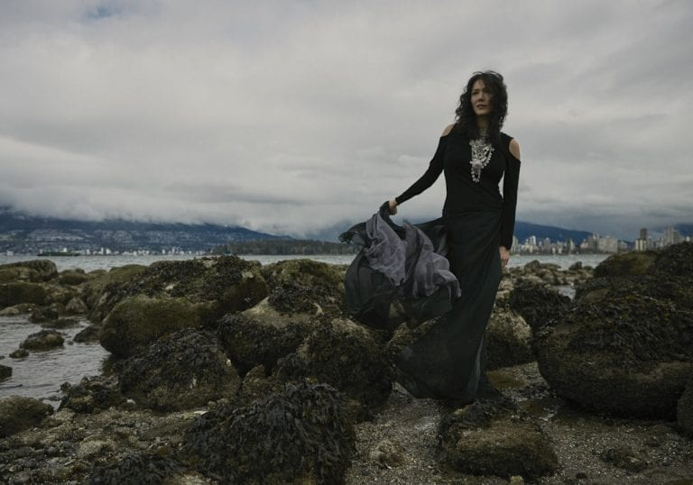 Outdoor portrait in natural light of a woman on a rock shoreline on a moody cloudy day, wearing a billowing chiffon skirt and the hair blowing her curls around her face by Vancouver contemporary portrait photographer Angela McConnell