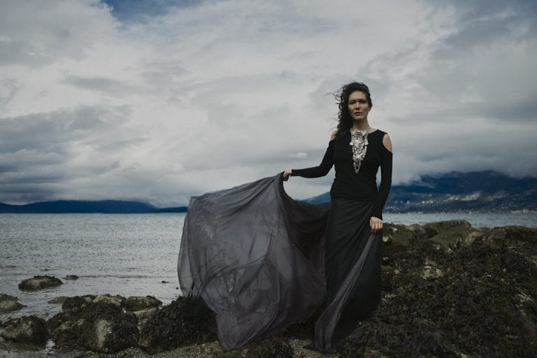 Outdoor portrait in natural light of a woman on a rocky shoreline wearing a large silver breastplate necklace and long chiffon skirt billowing in the wind by Vancouver contemporary portrait photographer Angela McConnell
