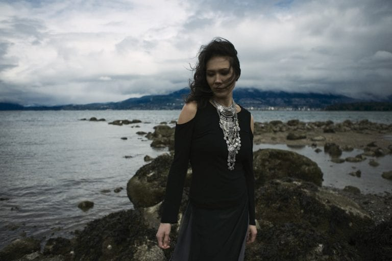 Outdoor portrait in natural light of a woman on a rocky shoreline with moody cloudy skies and the wind blowing her curls into her face by Vancouver contemporary portrait photographer Angela McConnell
