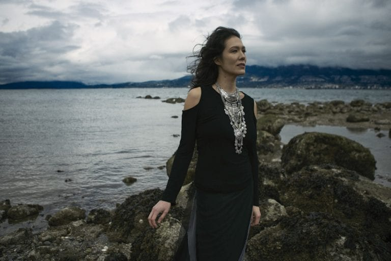 Outdoor portrait in natural light of a woman on a rocky shoreline wearing a larger silver breastplate necklace standing facing the wind as it blows her hair away from her face by Vancouver contemporary portrait photographer Angela McConnell
