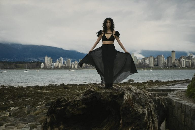 Outdoor portrait in natural light of a woman holding a long pleated skirt away from her body as it blows in the wind with English Bay in the background by Vancouver contemporary portrait photographer Angela McConnell