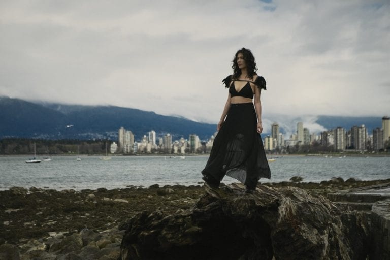 Outdoor portrait in natural light of a woman standing on a washed up log on a rocky shoreline looking out to sea with English Bay in the background by Vancouver contemporary portrait photographer Angela McConnell