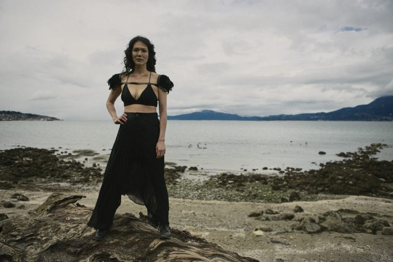Outdoor portrait in natural light of a woman on a rocky shoreline with a powerful stance looking straight at the camera by Vancouver contemporary portrait photographer Angela McConnell
