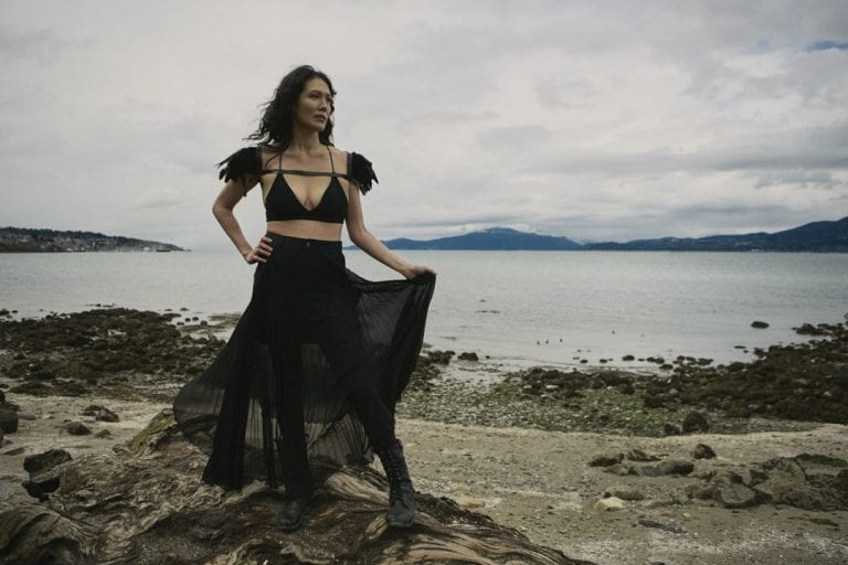 Outdoor portrait in natural light of a woman on a rocky shoreline holding her long skirt as it catches the wind by Vancouver contemporary portrait photographer Angela McConnell