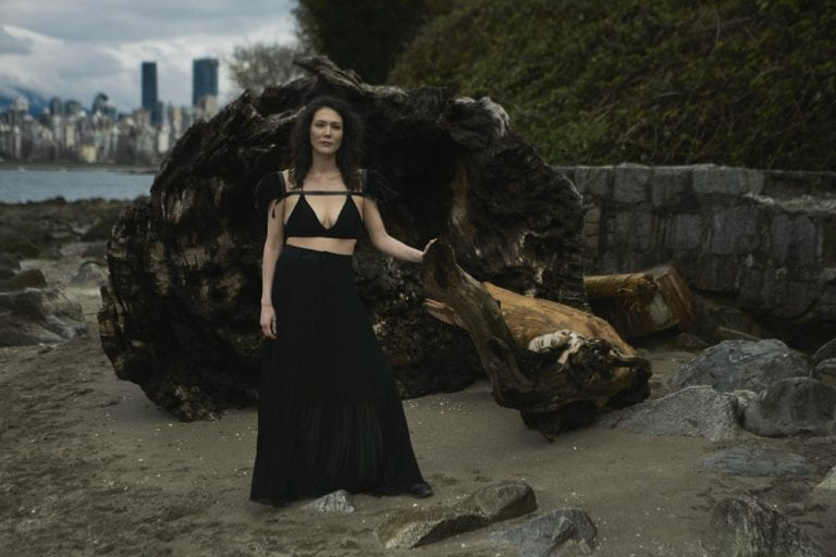 Outdoor portrait in natural light of a woman posing in front of a large washed up log on a rocky shoreline by Vancouver contemporary portrait photographer Angela McConnell