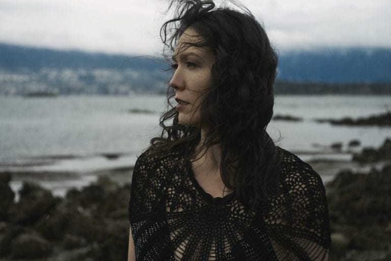 Outdoor portrait in natural light of a woman standing on a rocky shoreline with moody skies looking out over the water while the wind blows her curls around her face by Vancouver contemporary portrait photographer Angela McConnell