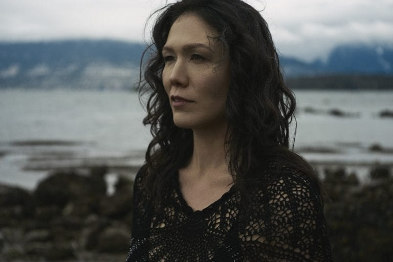 Outdoor portrait in natural light of a woman standing on a rocky shoreline with moody skies looking out over the water with her face framed by curls by Vancouver contemporary portrait photographer Angela McConnell
