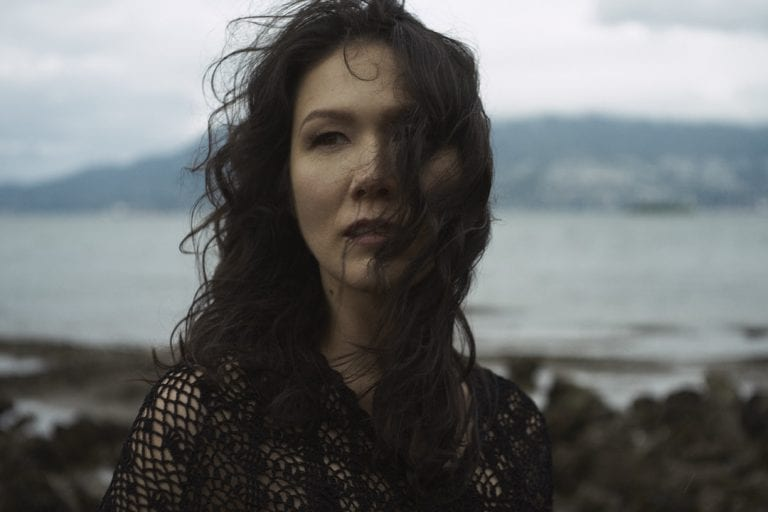 Outdoor portrait in natural light of a woman on a rocky shoreline looking away from the camera as the wind blows her curls across her face by Vancouver contemporary portrait photographer Angela McConnell