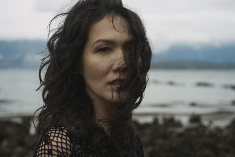 Outdoor portrait in natural light of a woman standing on a rocky shoreline with moody clouds looking straight at the camera while the wind blows her curls across her face by Vancouver contemporary portrait photographer Angela McConnell