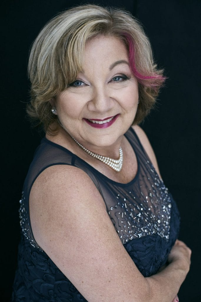 Studio portrait of an older woman in a sequinned navy dress and a pink stripe in her blonde hair smiling at the camera by Vancouver contemporary portrait photographer Angela McConnell