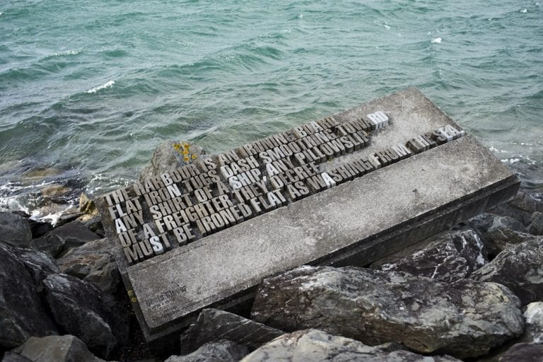 Image of a sculpture with a quote insert sitting on the rocks at the edge of Wellington Harbour with windswept water in the background